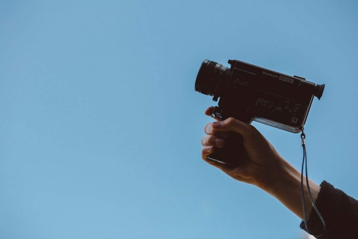This is the arm of someone holding a video camera at the sky