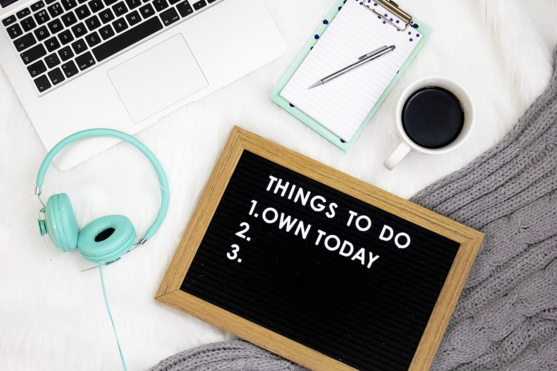 "teal headphones, coffee a laptop and a sign that says ""Things to do: Own today"""